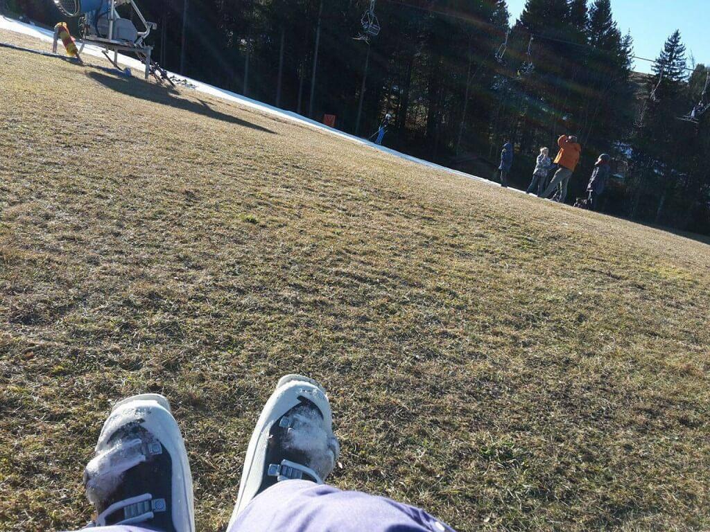 Mit Skistiefeln auf der grünen Wiese beim Sonnen