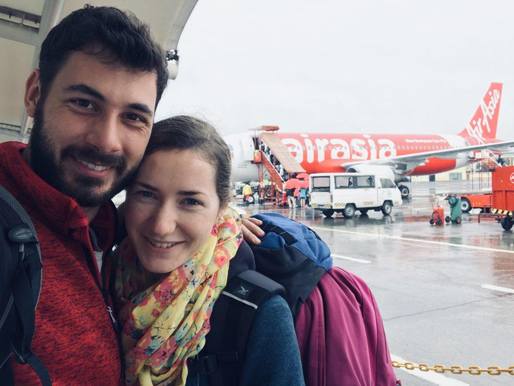 Nur mit Handgepäck reisen - Andrea und Bene stehen vor einem Flugzeug